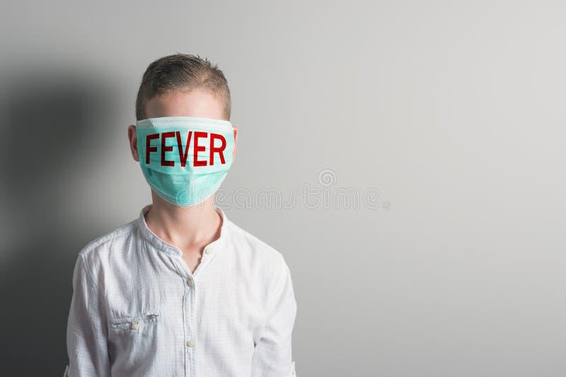 Menino em uma máscara médica com FEBRE vermelha da inscrição em sua cara no fundo brilhante fotos de stock