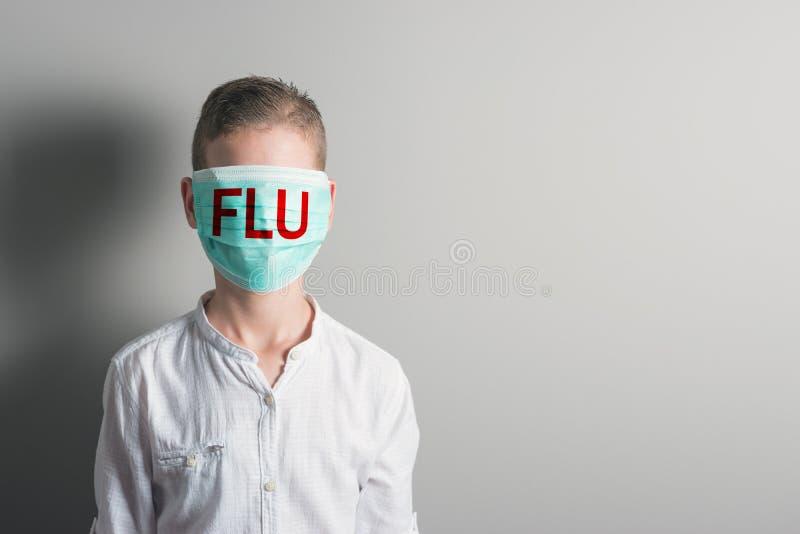 Menino em uma máscara médica com GRIPE vermelha da inscrição em sua cara no fundo brilhante imagens de stock royalty free