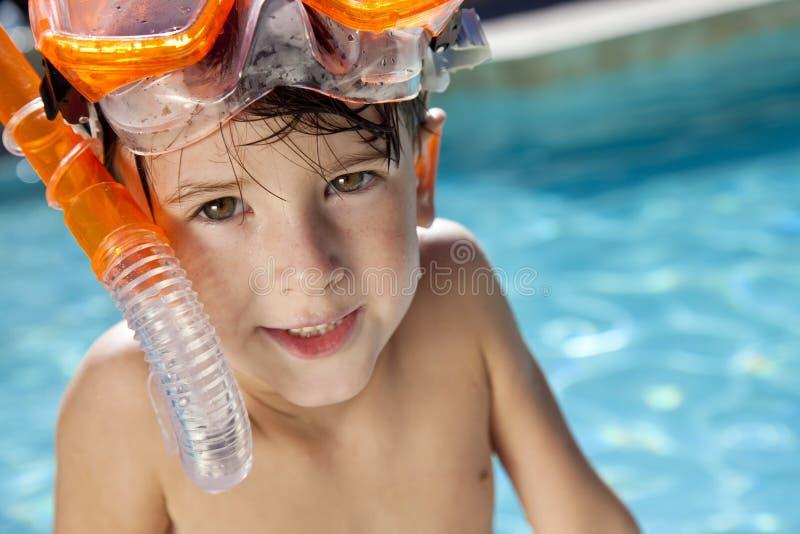 Menino em uma piscina com óculos de proteção e Snorkel foto de stock royalty free