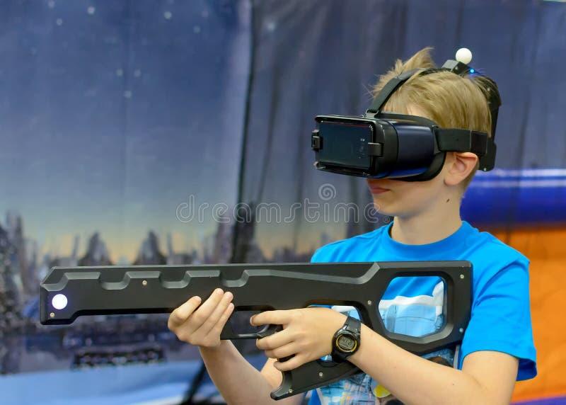Menino em vidros da realidade virtual com arma fotos de stock