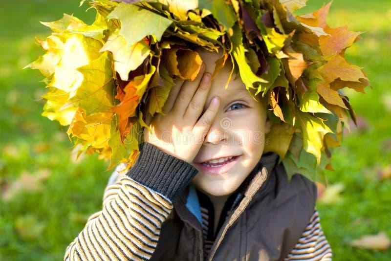 Menino emocional em uma grinalda das folhas de outono fotos de stock