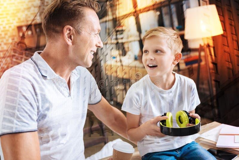 Menino emocional que olha seu pai ao guardar fones de ouvido grandes fotografia de stock royalty free