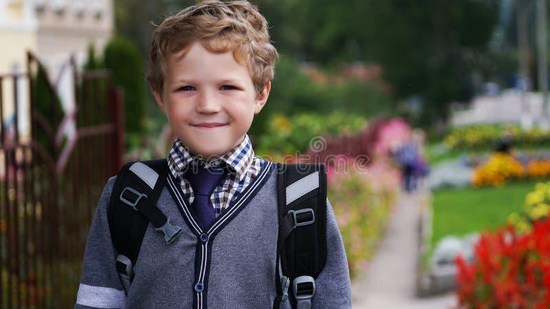 Menino encaracolado pequeno feliz da criança com trouxa ou sacola em seu primeiro dia à escola ou ao berçário Criança fora em ens imagem de stock