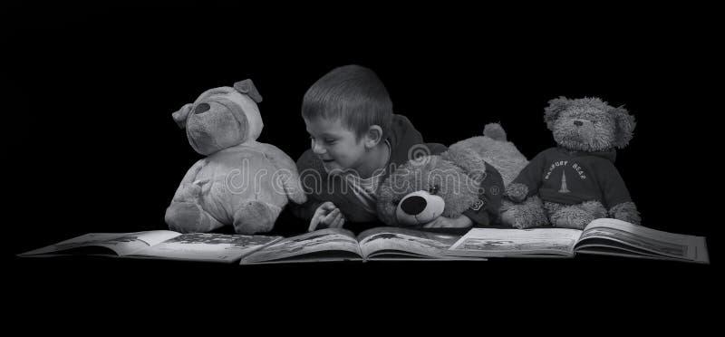 Menino engraçado com os bichos de pelúcia que leem um livro antes do tempo AR da cama foto de stock royalty free