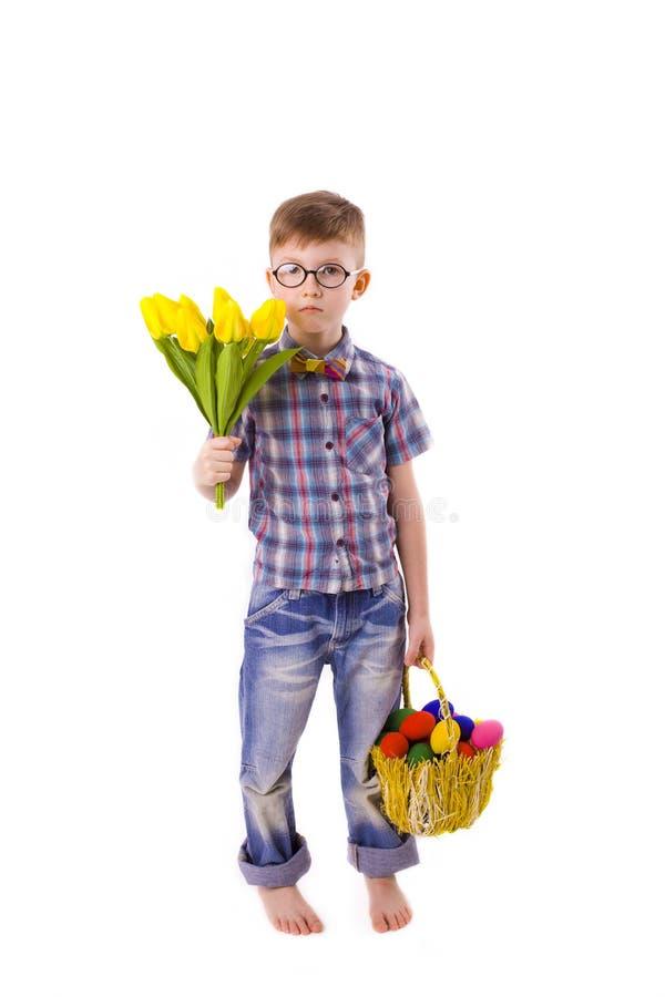 Menino engraçado com um ramalhete das tulipas e a cesta da Páscoa dos ovos foto de stock royalty free
