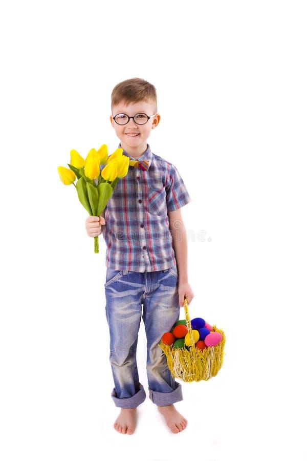 Menino engraçado com um ramalhete das tulipas e a cesta da Páscoa dos ovos imagens de stock royalty free