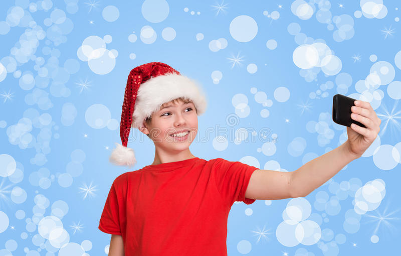 Menino engraçado do preteen no chapéu de Santa que faz o selfie no holida do Natal fotografia de stock