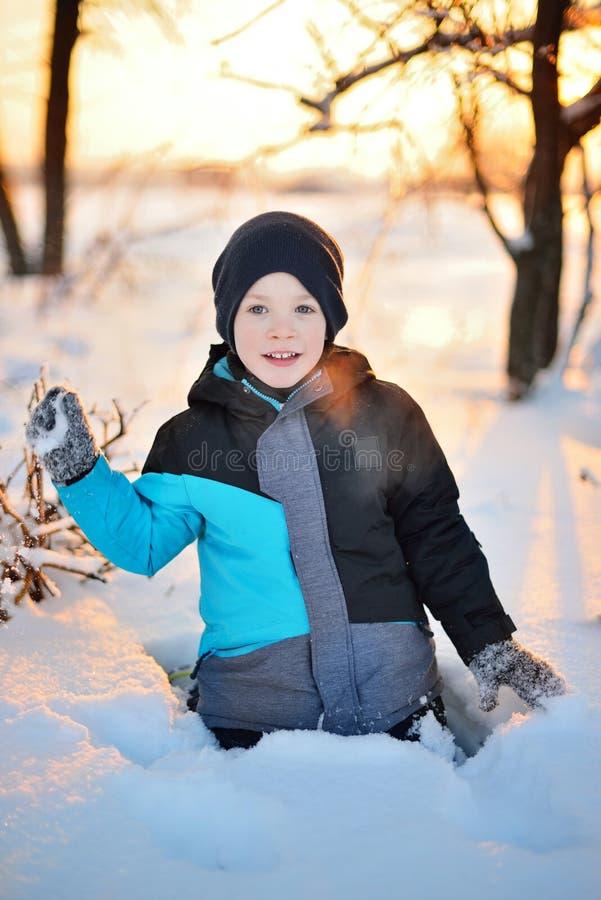 Menino engraçado pequeno adorável do retrato na roupa do inverno que tem o divertimento com neve, fora durante a queda de neve La fotos de stock