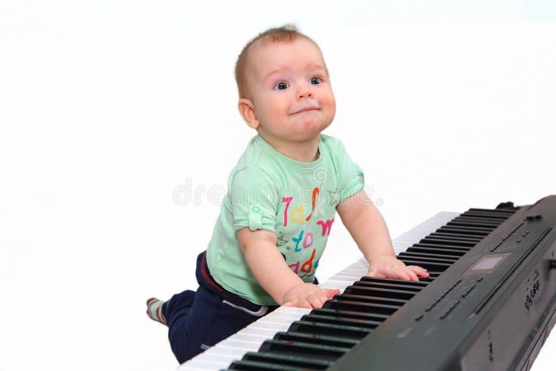 Menino engraçado pequeno que joga o piano bonde fotografia de stock royalty free