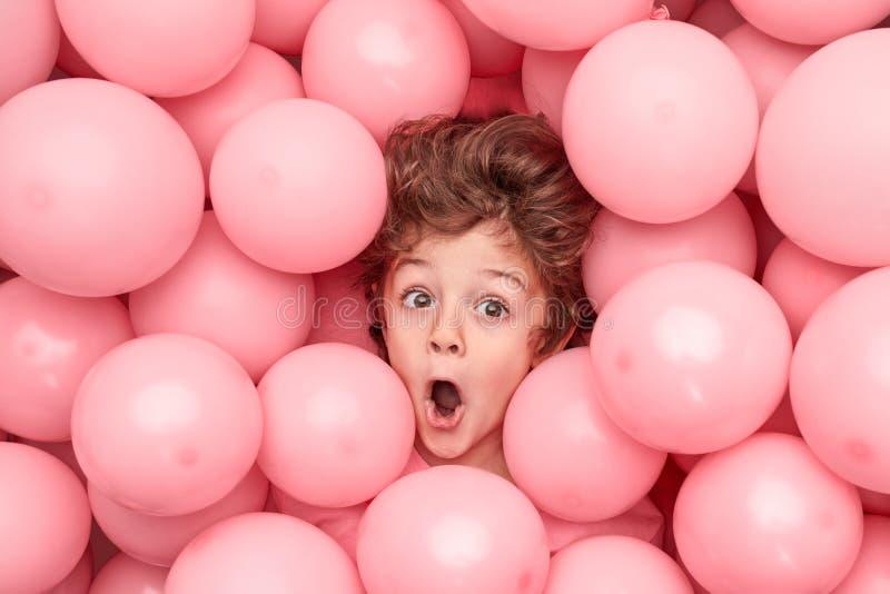 Menino engraçado sob balões cor-de-rosa imagens de stock royalty free