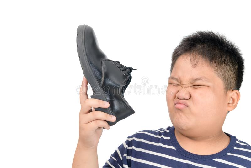Menino enojado que guarda um par de sapatas de couro f?tidos fotos de stock royalty free