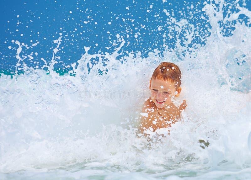 Menino entusiasmado bonito que tem o divertimento nas ondas, férias de verão fotos de stock