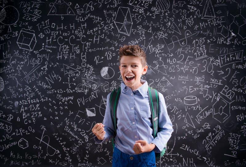 Menino entusiasmado e vitorioso contra o quadro-negro com matemático foto de stock