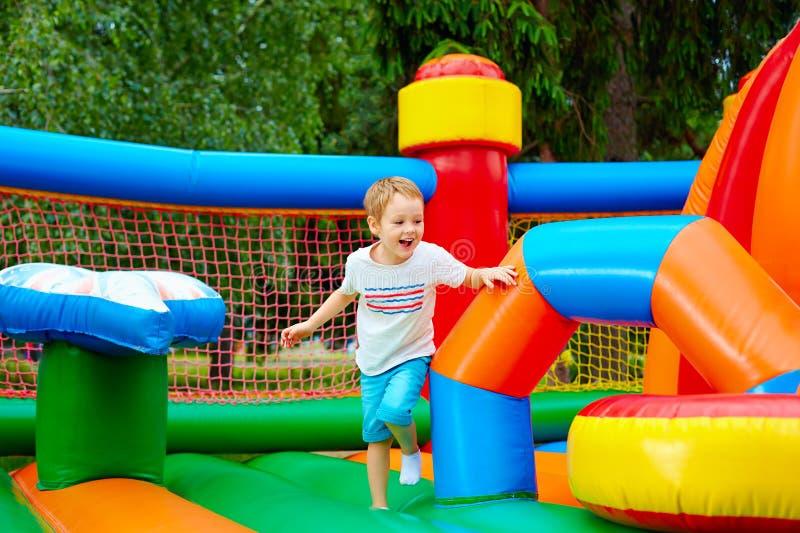 Menino entusiasmado feliz que tem o divertimento no campo de jogos inflável da atração foto de stock royalty free
