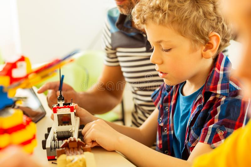 Menino entusiasmado feliz que tenta construir brinquedos fotografia de stock royalty free