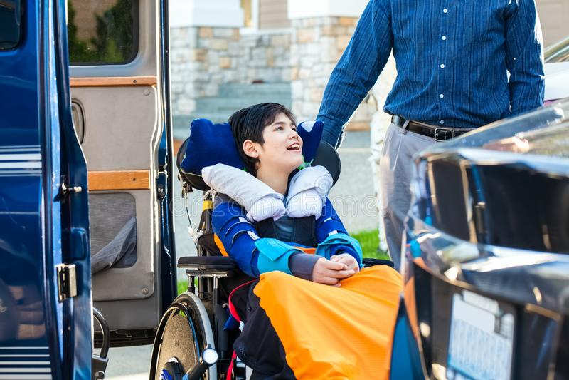 Menino especial das necessidades na cadeira de rodas no elevador da desvantagem do veículo imagem de stock