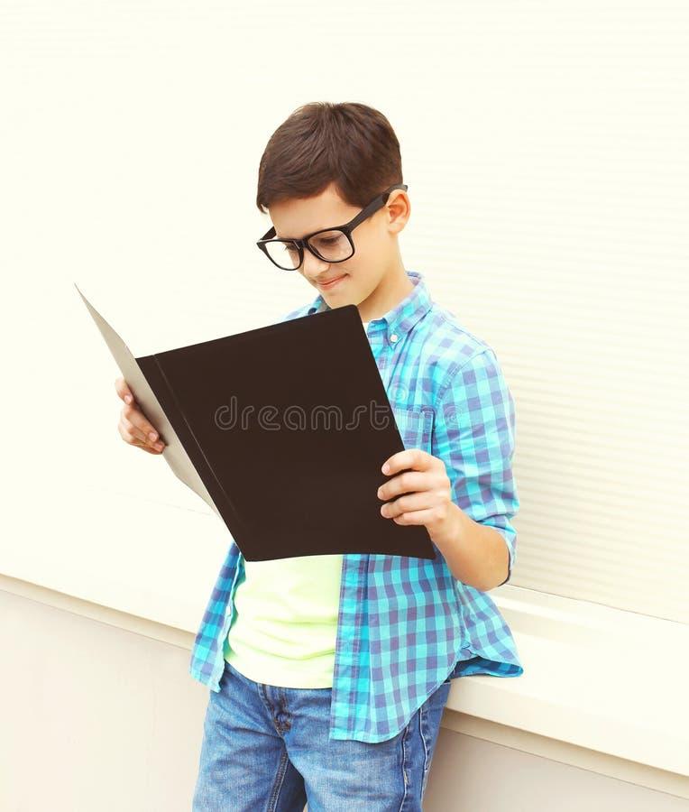 Menino esperto bonito do adolescente nos vidros que olham ou no livro de leitura foto de stock royalty free