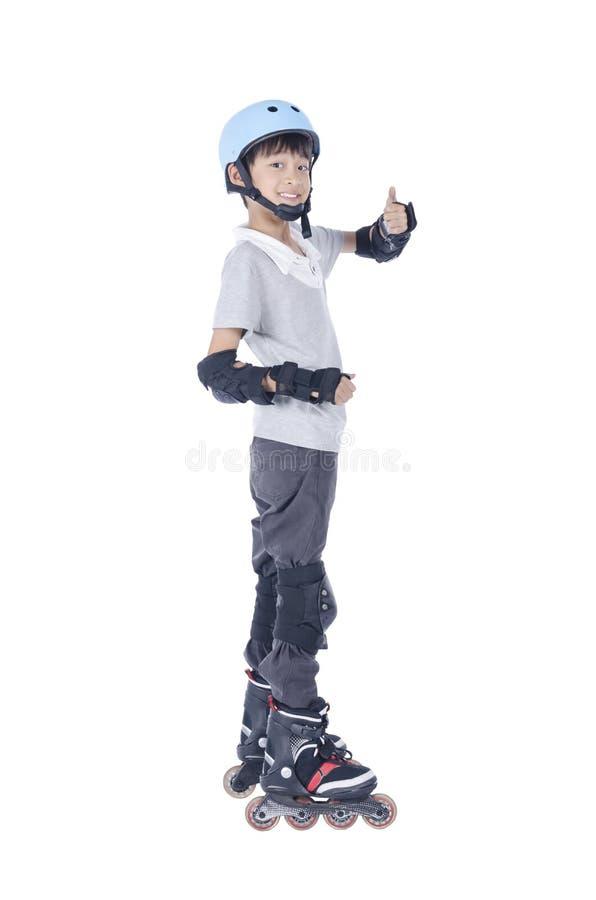 Menino esperto que joga patins de rolo fotos de stock