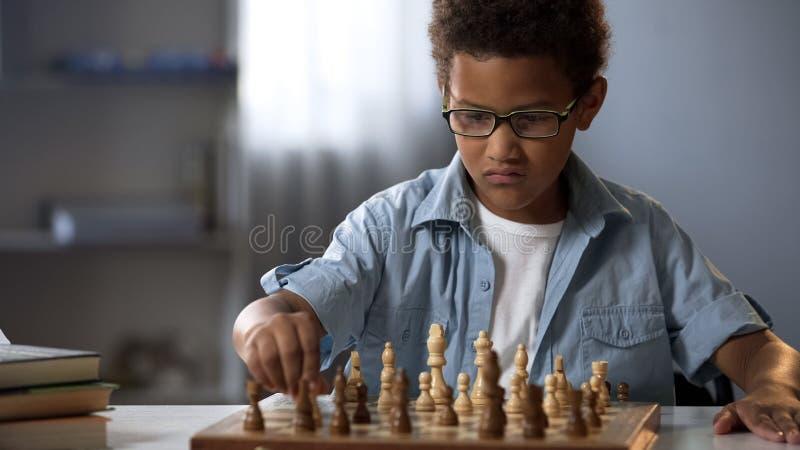 Menino esperto que joga a xadrez que pensa com cuidado com cada movimento, jogo lógico imagens de stock