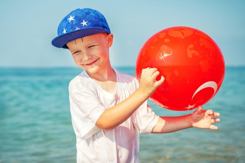 Menino europeu de sorriso no mar com a bola da bandeira turca Criança feliz no fundo da água do mar azul Férias de verão em Turqu fotos de stock royalty free