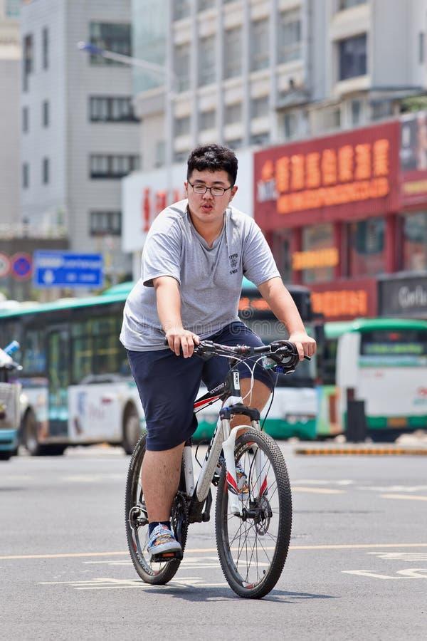 Menino excesso de peso em um Mountain bike, Kunming, China imagem de stock royalty free