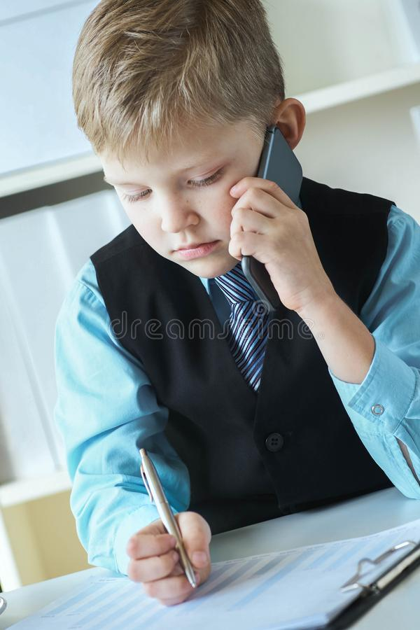 Menino executivo seguro pequeno do chefe do homem de negócios que faz anotações e negociações no telefone que senta-se na mesa co foto de stock royalty free