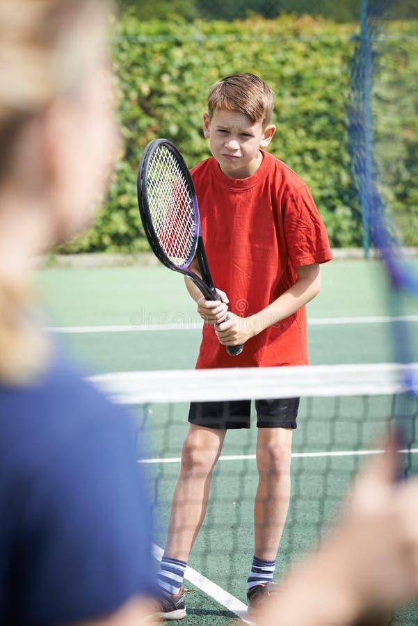 Menino fêmea de Giving Lesson To do treinador de tênis fotos de stock