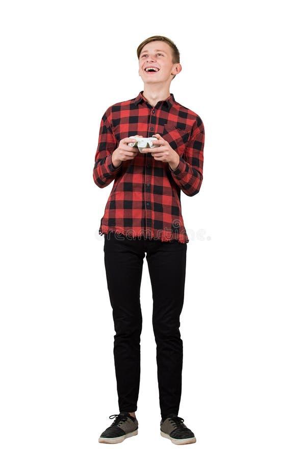 Menino fascinado jogando videogame isolado sobre fundo branco O adolescente animado aguenta todos os ouvidos segurando um joystic foto de stock royalty free