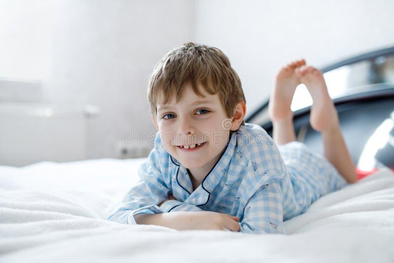 Menino feliz adorável da criança após o sono em sua cama branca do hotel no nightwear colorido Aluno na família fotos de stock