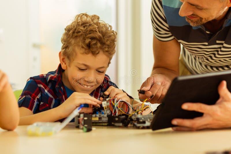 Menino feliz alegre que aprende construir brinquedos fotografia de stock royalty free