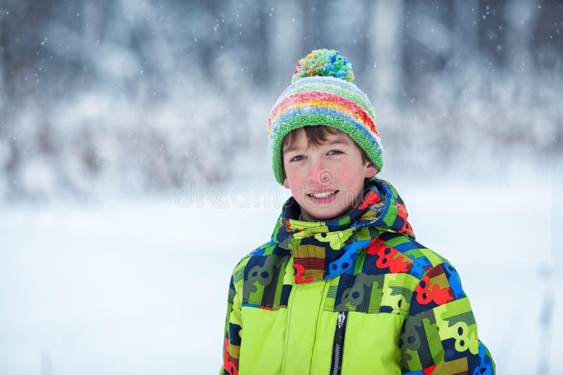 Menino feliz alegre que joga no parque do inverno, foto de stock royalty free