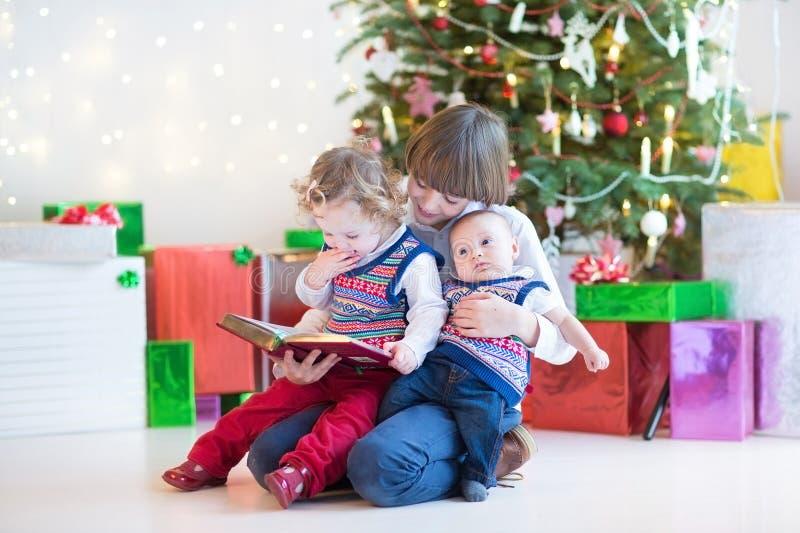 Menino feliz bonito que lê a seus irmã da criança e irmão recém-nascido do bebê em uma sala escura com árvore de Natal imagens de stock