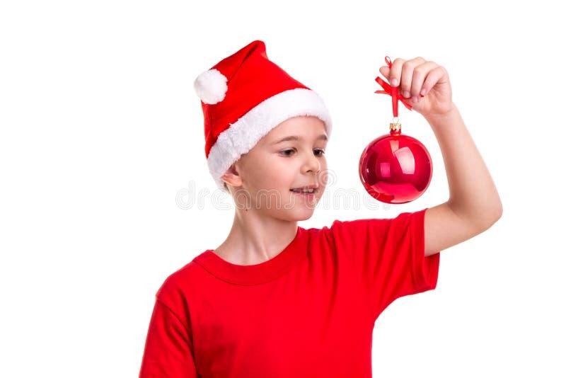 Menino feliz, chapéu de Santa em sua cabeça, guardando e olhando a bola vermelha do Natal Conceito: Natal ou ano novo feliz imagem de stock