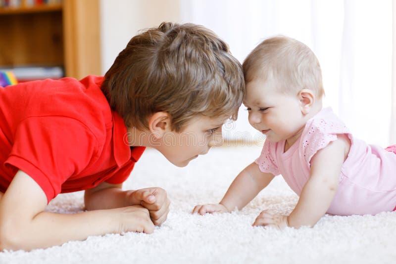 Menino feliz com bebê recém-nascido, irmã bonito da criança siblings Irmão e bebê que jogam junto fotos de stock royalty free