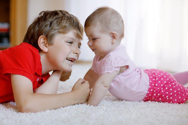 Menino feliz com bebê recém-nascido, irmã bonito da criança siblings Irmão e bebê que jogam junto imagem de stock