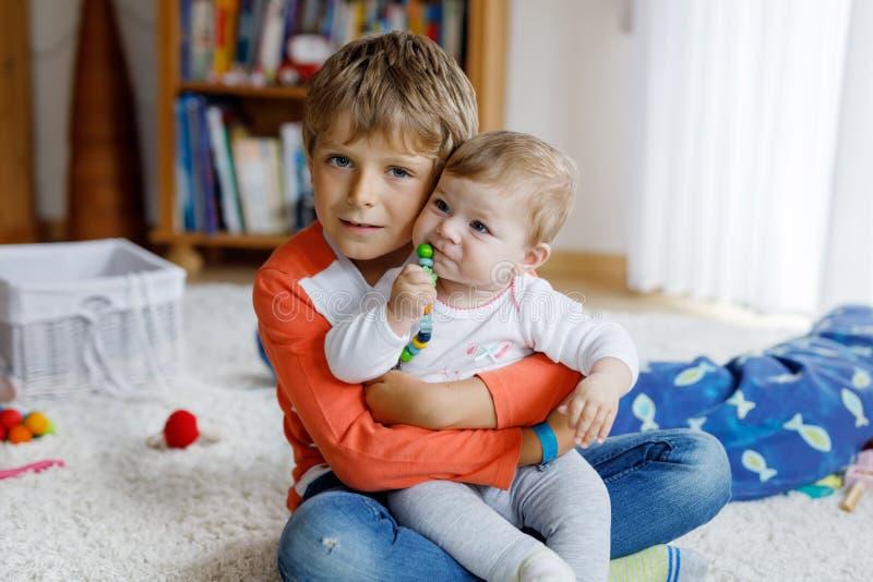 Menino feliz com bebê recém-nascido, irmã bonito da criança siblings Irmão e bebê que jogam junto Criança mais idosa imagens de stock