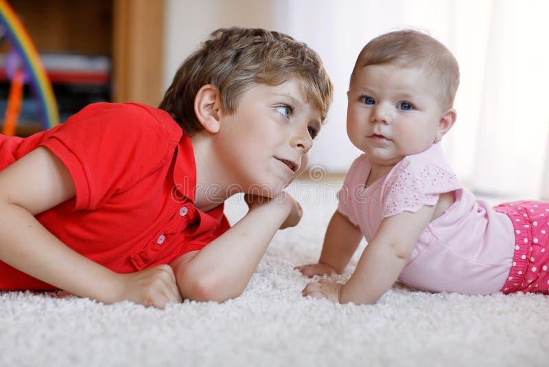 Menino feliz com bebê recém-nascido, irmã bonito da criança siblings Irmão e bebê que jogam junto Criança mais idosa fotos de stock royalty free