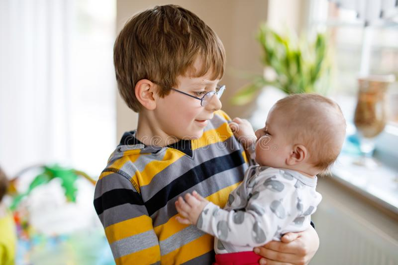 Menino feliz com bebê recém-nascido, irmã bonito da criança siblings Irmão que guarda o bebê no braço Ligamento das crianças imagem de stock