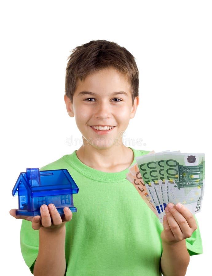 Menino feliz com dinheiro e casa em sua mão fotos de stock