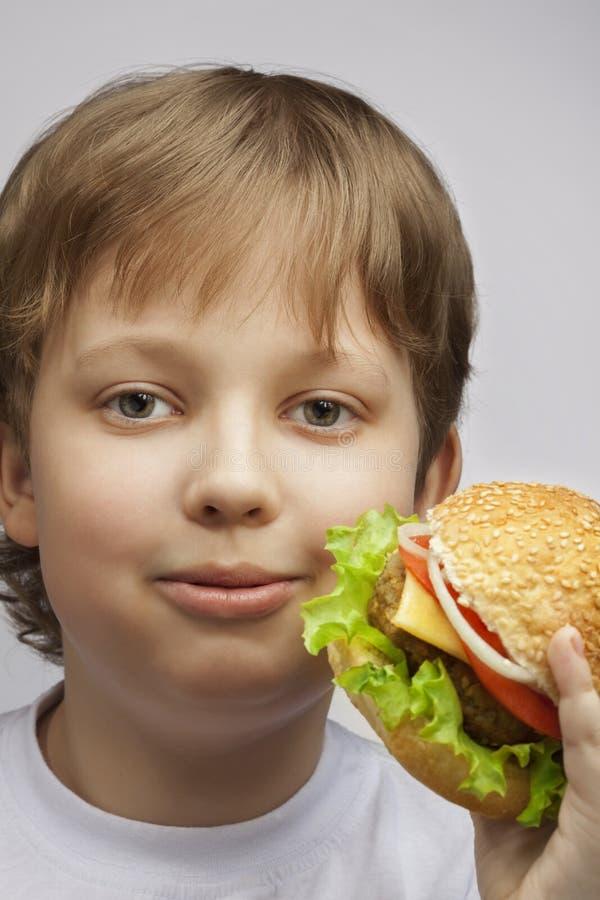 Menino feliz com hamburguer Adolescente com um sanduíche delicioso em um w imagem de stock royalty free
