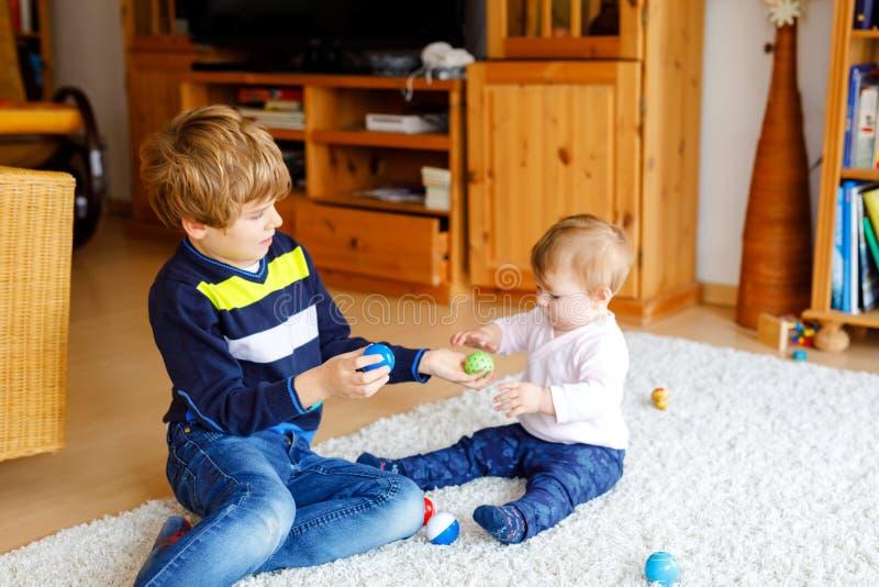 Menino feliz com o bebê pequeno bonito, irmã bonito da criança siblings Irmão e bebê que jogam junto Criança mais idosa imagens de stock royalty free