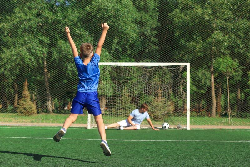 Menino feliz com seu paizinho que joga o futebol no passo do futebol imagens de stock