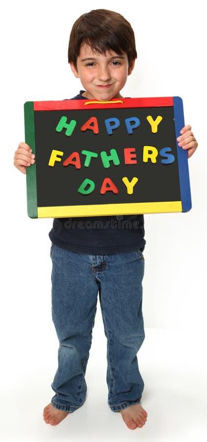 Menino feliz com sinal feliz do dia de pais fotografia de stock