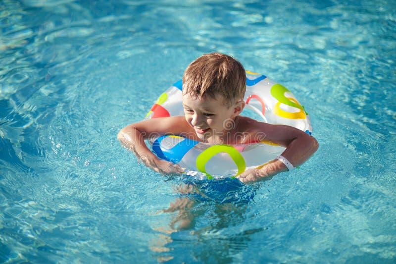 Menino feliz com um anel de vida que aprecia na piscina fotos de stock