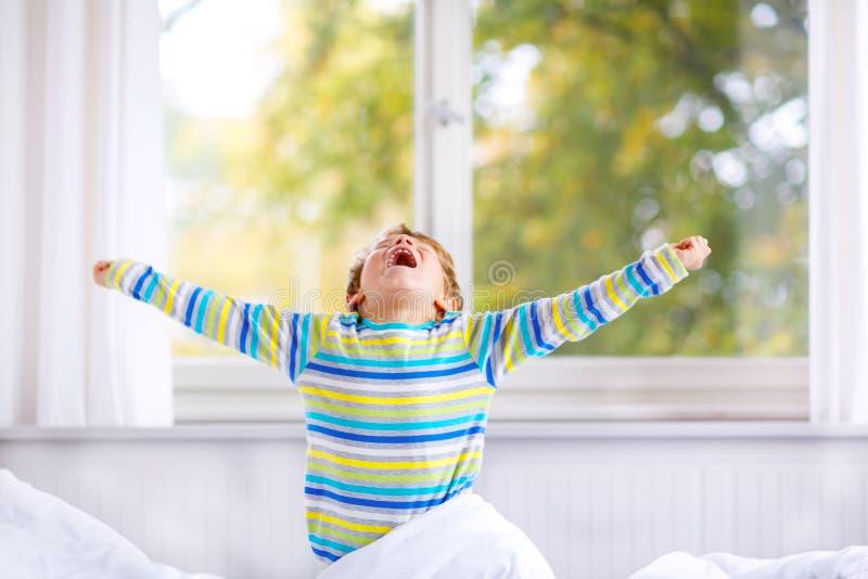 Menino feliz da criança após o sono na cama no nightwear colorido fotos de stock