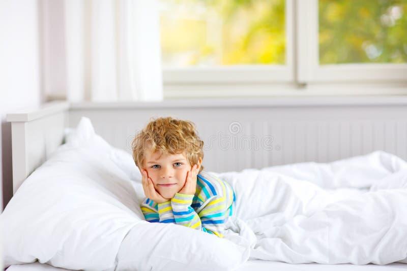 Menino feliz da criança após o sono na cama no nightwear colorido imagens de stock
