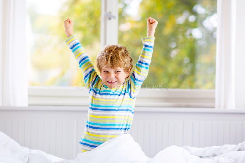 Menino feliz da criança após o sono na cama no nightwear colorido imagem de stock royalty free