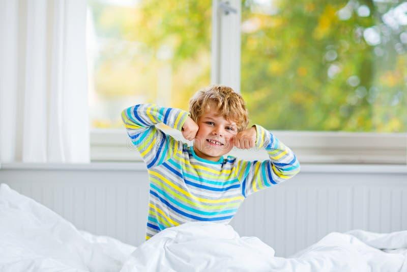 Menino feliz da criança após o sono na cama no nightwear colorido fotografia de stock