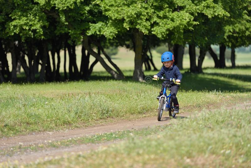 Menino feliz da criança de 5 anos que têm o divertimento na floresta da mola com um bicy imagem de stock
