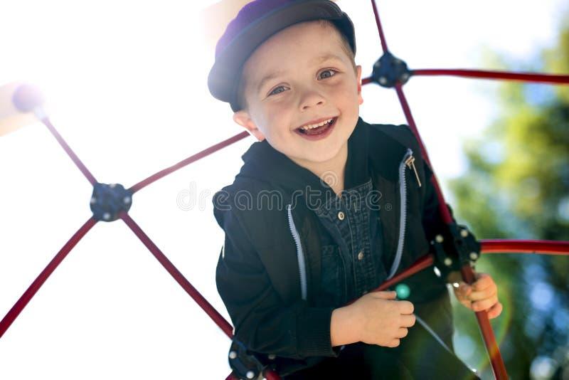 Menino feliz da criança pequena escalado no campo de jogos fotografia de stock royalty free